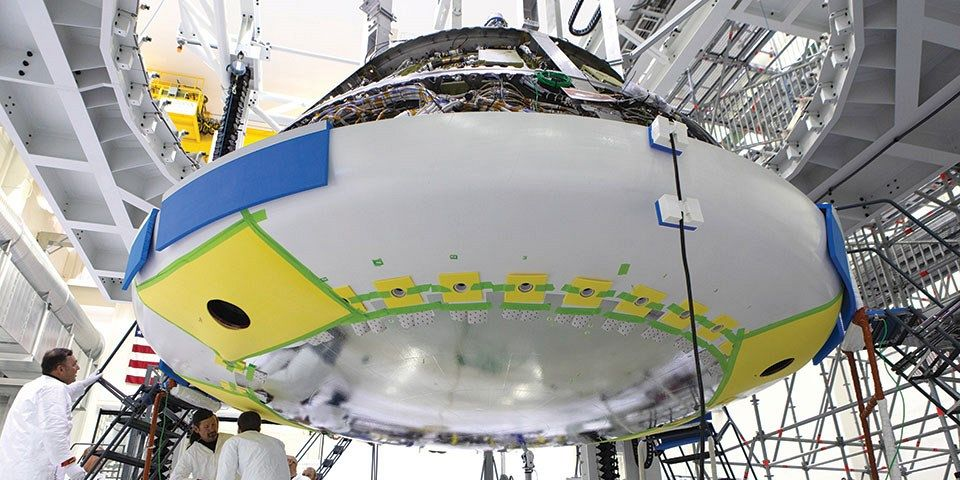 Lockheed Martin engineers and technicians install the titanium heat shield to the Orion crew module on 25 July 2018 at NASA's Kennedy Space Center in Florida. Photo: NASA/Kim Shiflett